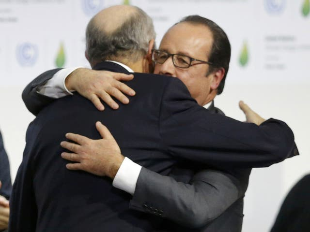 French President Francois Hollande (R) embraces French Foreign Affairs Minister Laurent Fabius, President-designate of COP21