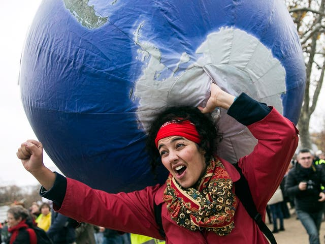 A demonstrator in front of the Eiffel Tower during COP21. The Paris Agreement creates a subtle but powerful mechanism to ratchet up the carbon-cutting commitments of all countries until they reach the point where global warming can indeed be held in check