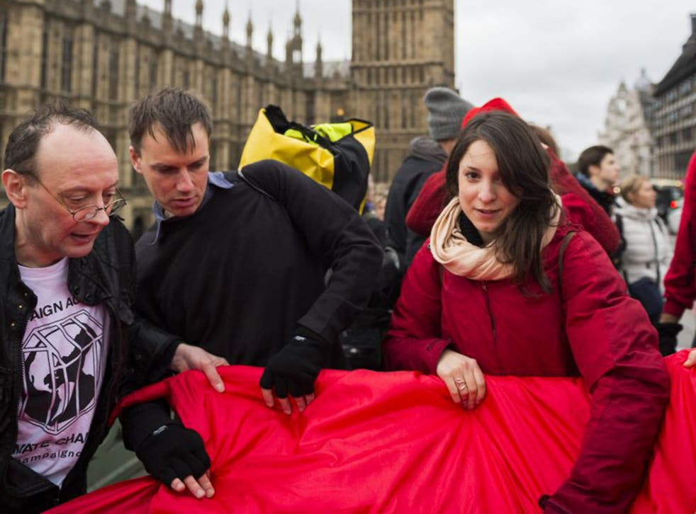 Climate change activists campaigning to limit emissions with a red banner to symbolise a 'red line' on Westminster Bridge on Saturday