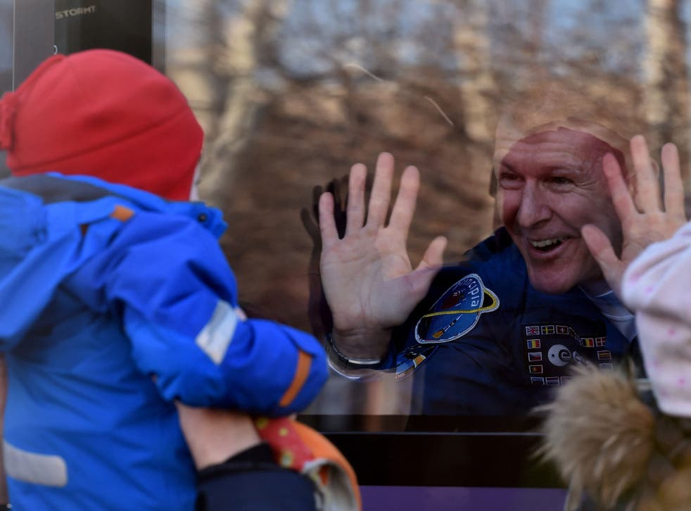 British astronaut Tim Peake waves from a bus during a sending-off ceremony at the Baikonur Cosmodrome on December 15, 2015.