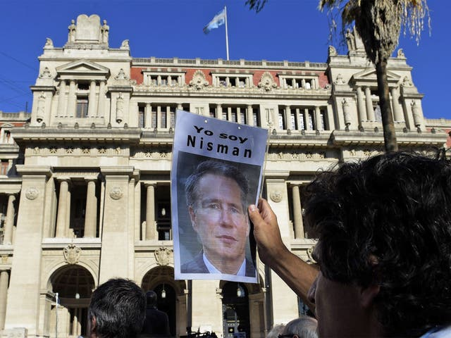 A man holds a portrait of late Argentine prosecutor Alberto Nisman during a demonstration in demand of justice, in front of the law court in Buenos Aires, earlier this year