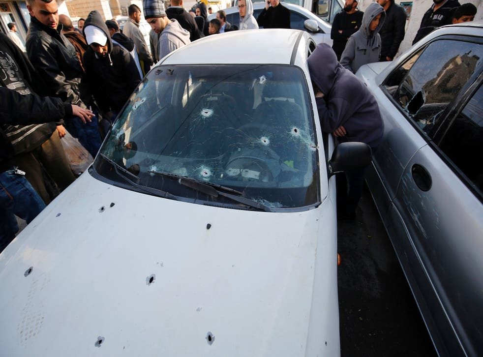 Palestinians stand next to a car, used by Palestinians in an attempted ramming attack against Israeli soldiers, in the Qalandia refugee camp near the West Bank city of Ramallah on December 16, 2015.