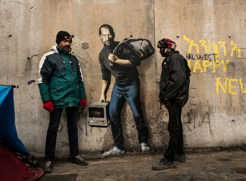 Two men stand next to Banksy's Steve Jobs mural in the Calais migrant camp