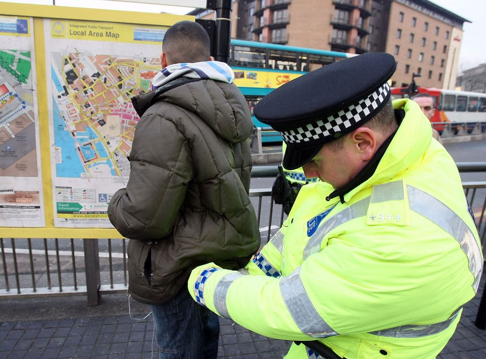 Police officers, combating potential knife-crime, stop and search people arriving in Liverpool by bus for traditional celebrations ahead of the festive period