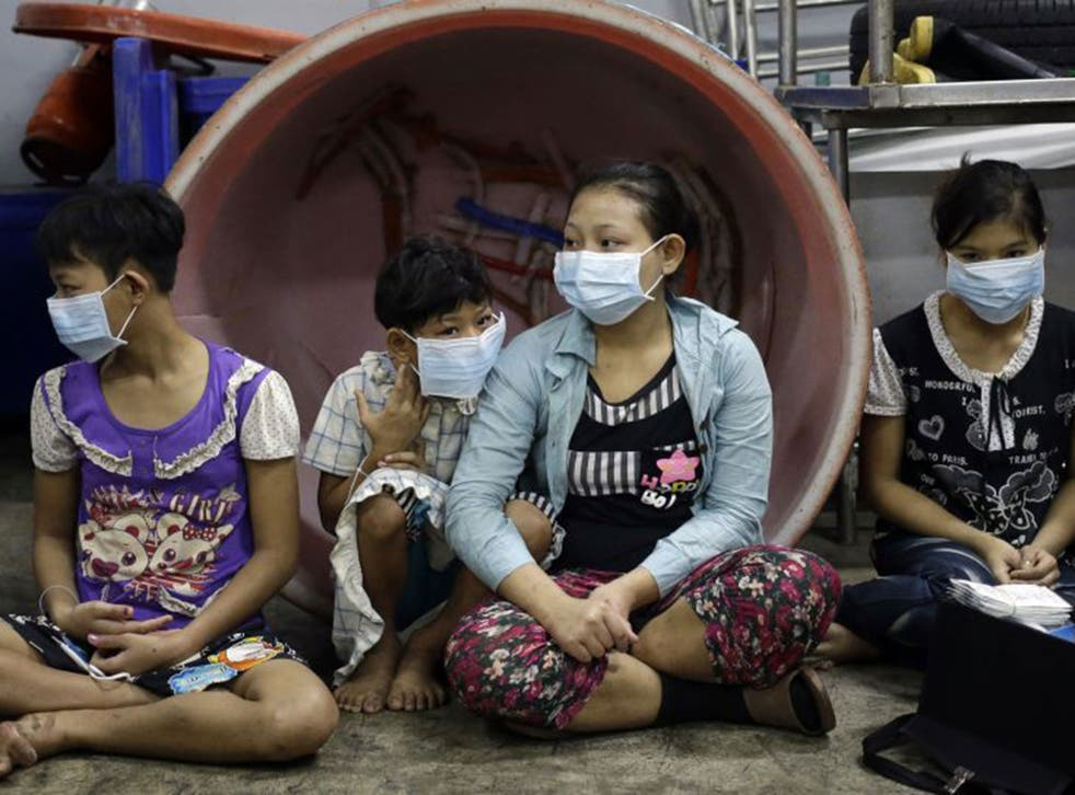 Eae Hpaw, 16, center, an undocumented child worker, sits with children and teenagers to be registered by officials during a raid on a shrimp shed in Samut Sakhon, Thailand.