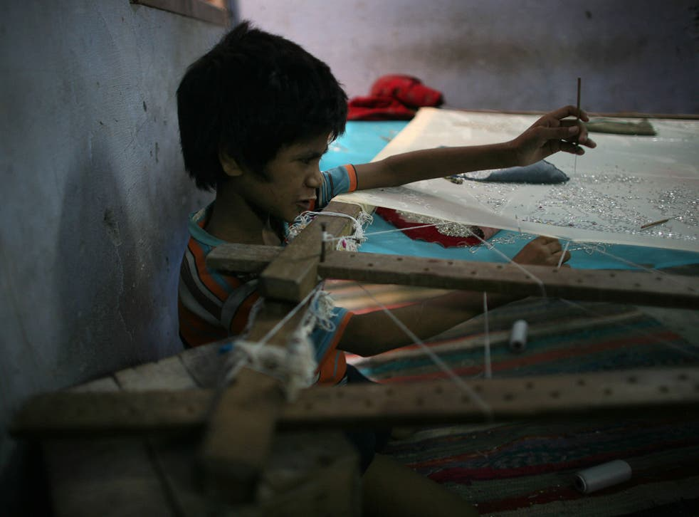 An Indian child sews sequins on to a garment in a workshop in Delhi. Currently, children under 14 are allowed to work in 'non-hazardous' occupations