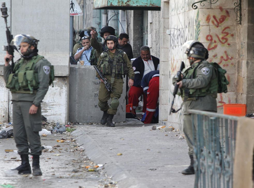 Israeli troops stand guard as medics treat a Palestinian woman hit with rubber attacks during an attempted attack on the army in Hebron in the West Bank