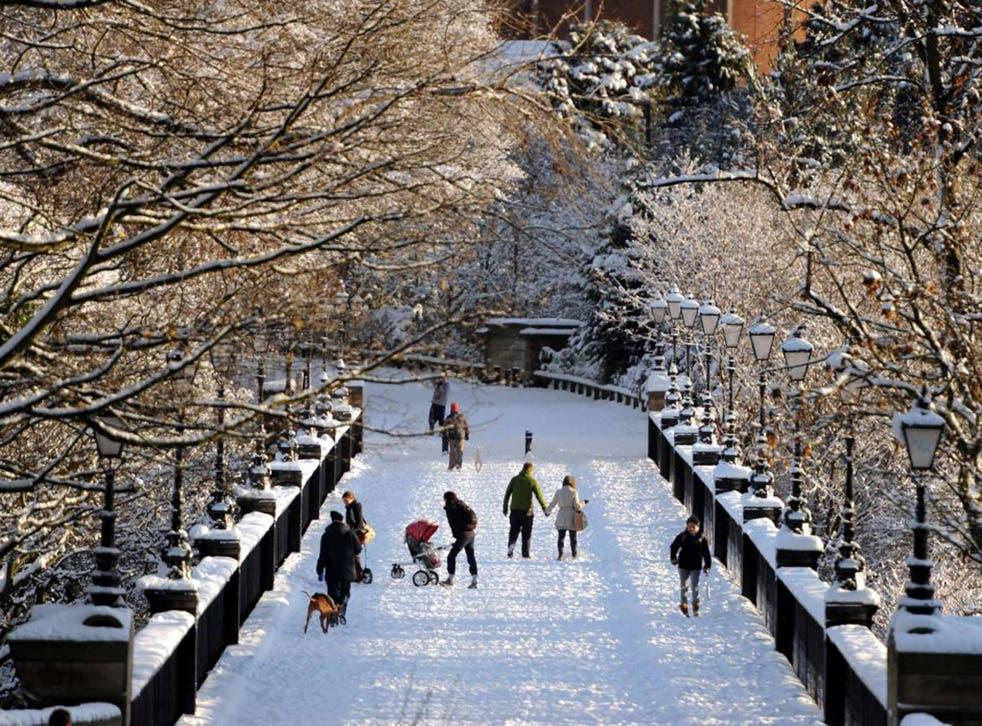 Walkers cross a snow-covered bridge