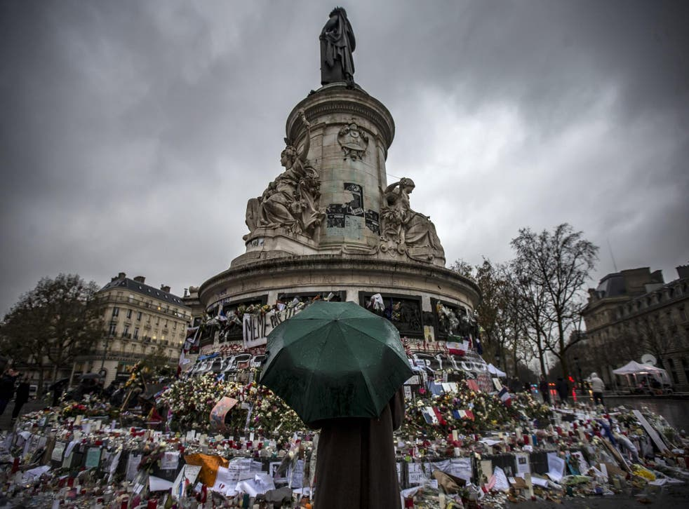 A pedestrian with an umbrella pauses in front of the memorial of candles and flowers for the victims of the 13 November Paris