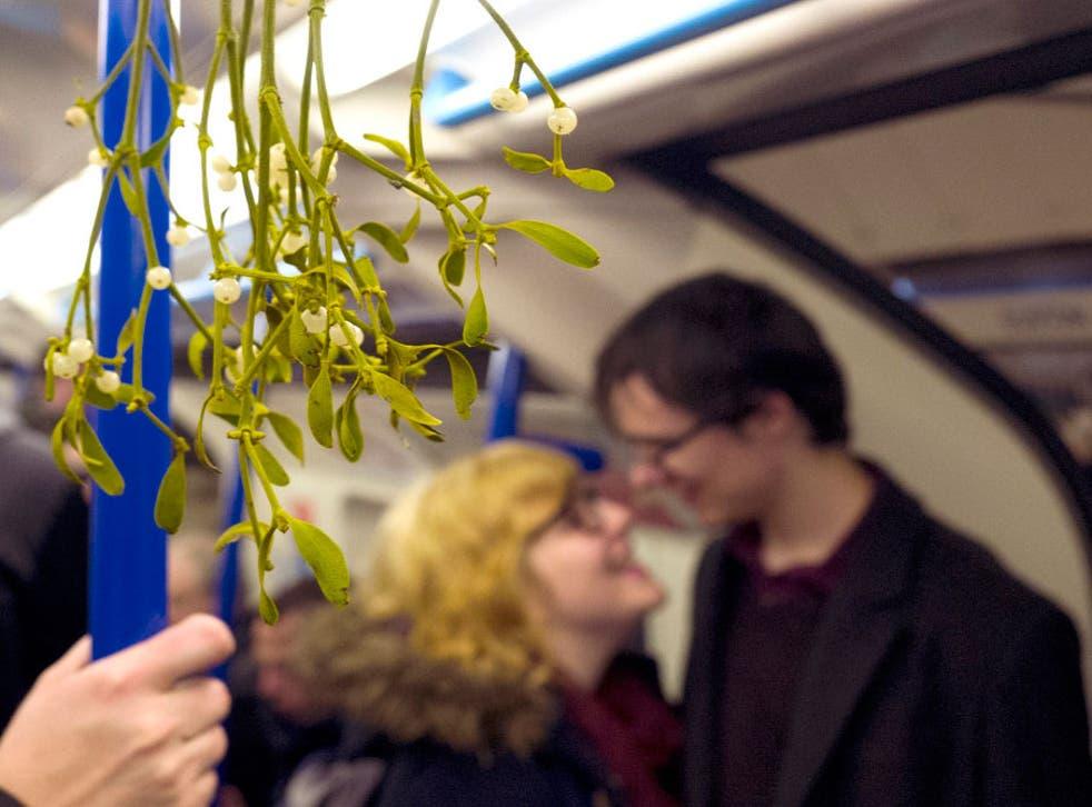 Commuters under mistletoe on the London Underground