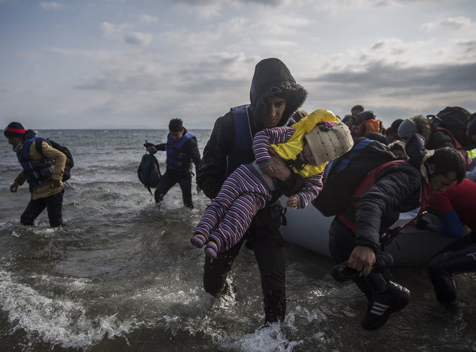 Refugees disembark from a dinghy after their arrival from Turkey on the Greek island of Lesbos, on Saturday, Dec. 12, 2015