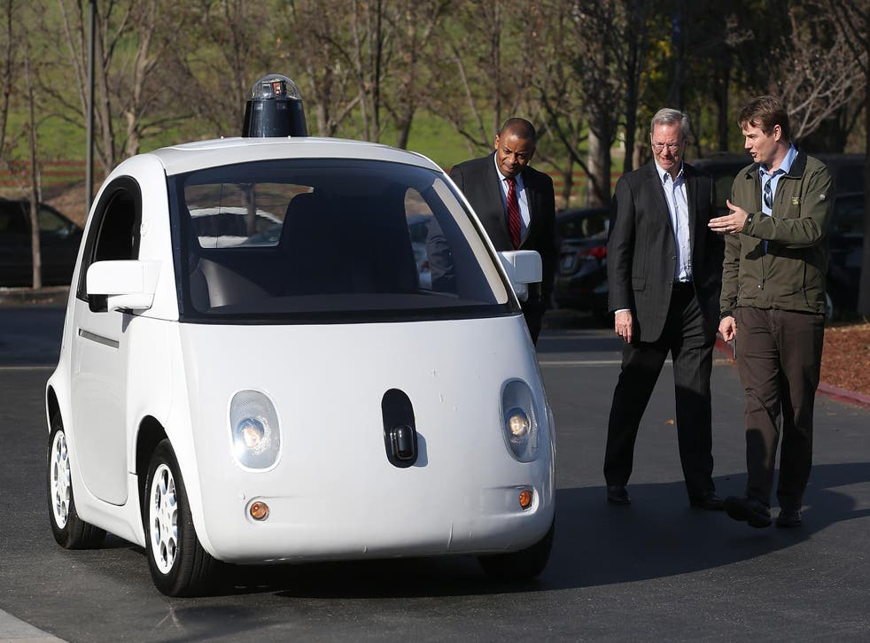 Chris Urmson, the head of Google's self-driving car project, shows one of the prototypes to US Transportation Secretary Anthony Foxx