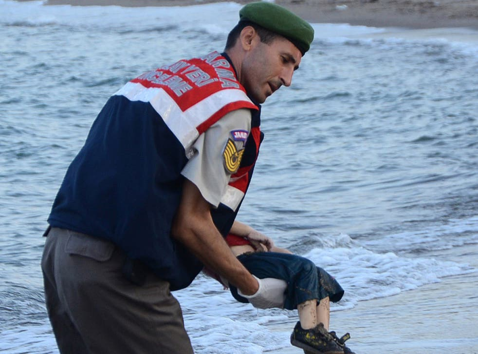 A Turkish police officer carries the body of Aylan Kurdi off the shores in Bodrum