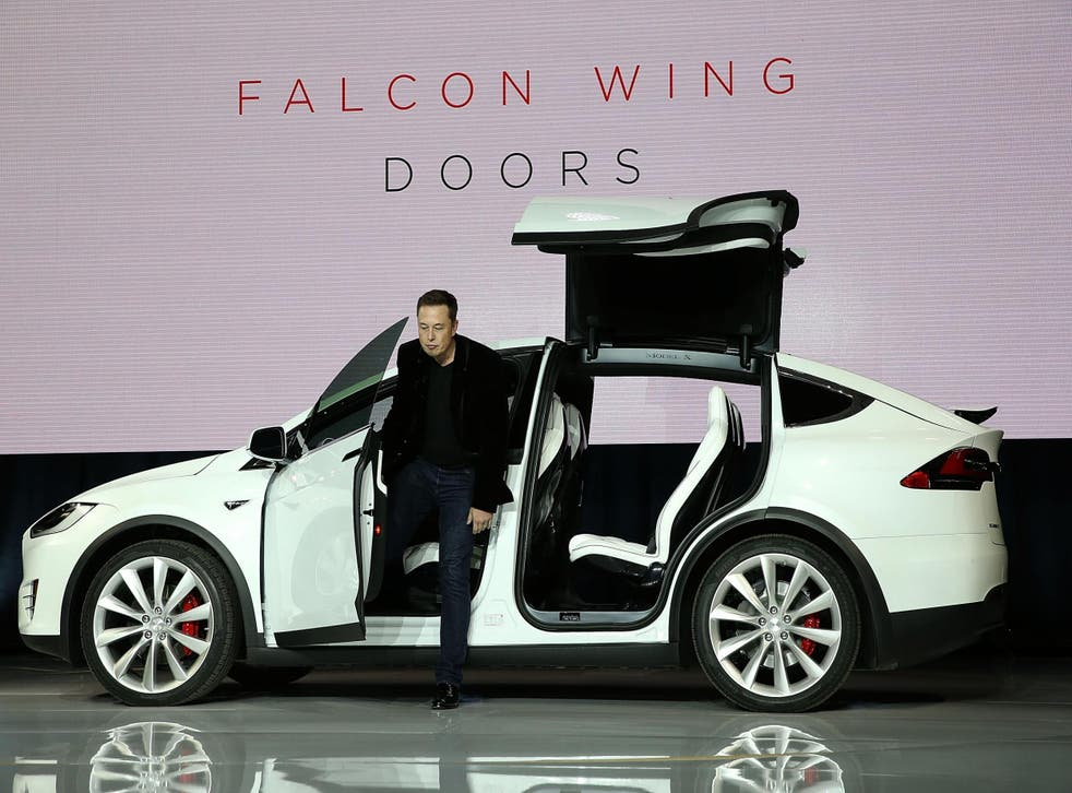 Tesla CEO Elon Musk steps out of a Tesla Model X SUV at the launch event in September 2015