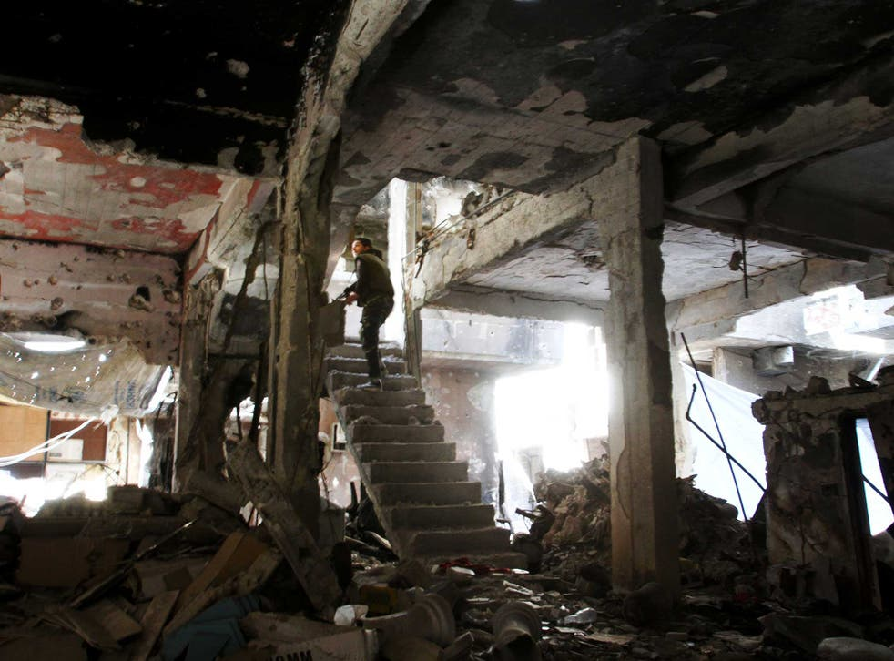 A sniper peers through the ruins of a building in Yarmouk refugee camp