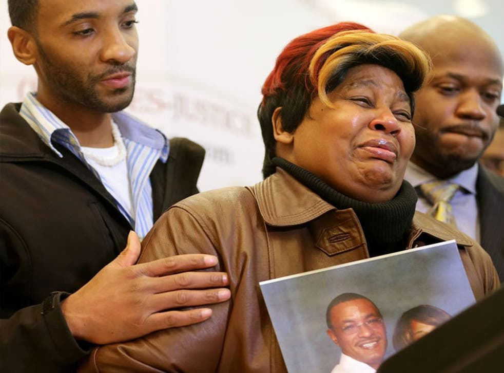 Cynthia Daniels is comforted by her son Bobby Daniels Jr. during a news conference about the death of  her husband, Bobby Daniels