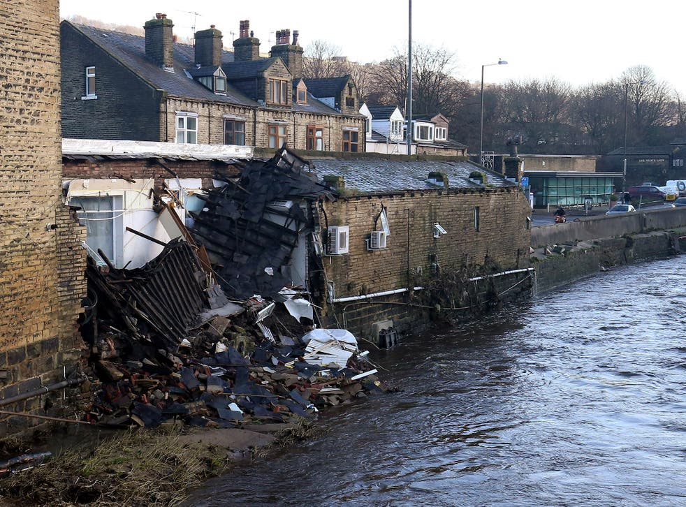 Part of a building collapsed into the river after yesterday's floods in Mythelmroyd, England