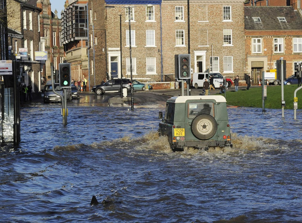 A Land Rover is driven through floodwater in York city centre, after the River Ouse and the River Foss burst their banks.