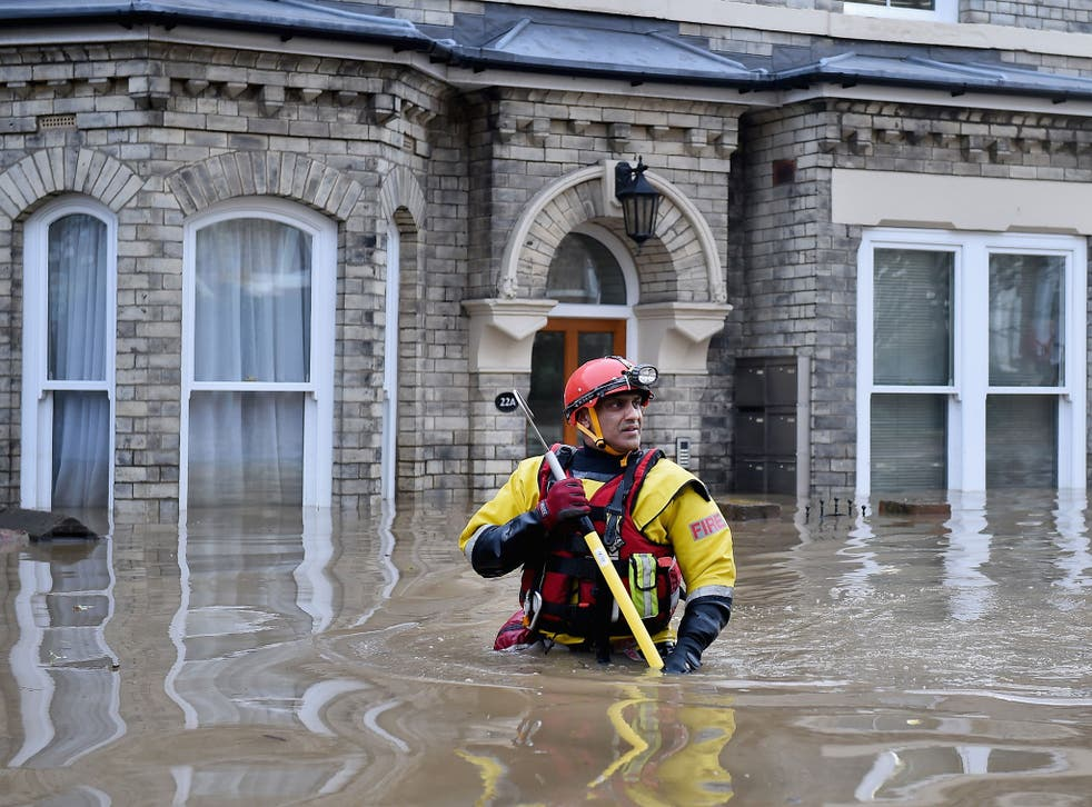 Rescue teams wade through flood waters that have inundated homes in the Huntington Road area of York after the River Foss burst its banks, on 28 December, 2015