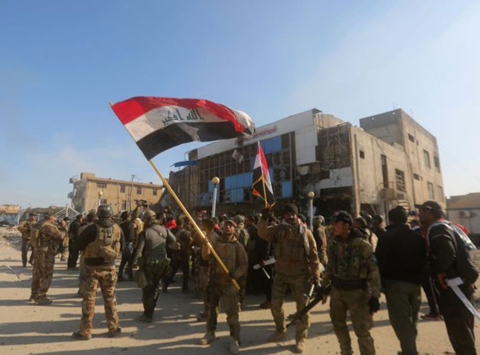 Iraqi security forces fly the national flag after they recaptured Ramadi