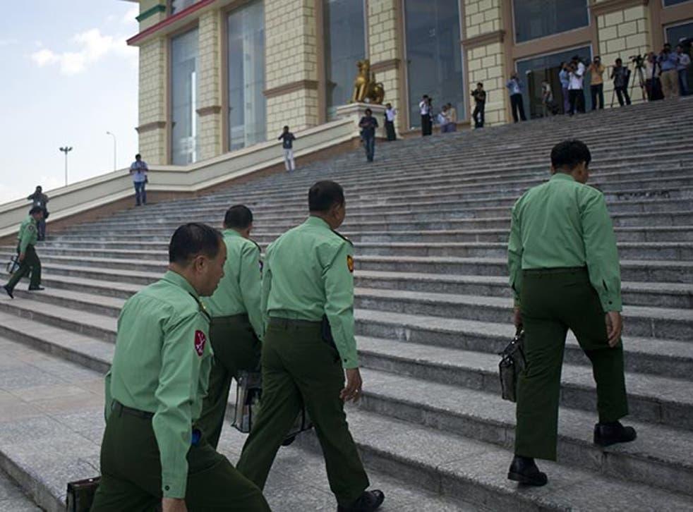 Military officials can be seen wearing the light green uniform