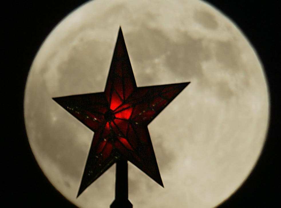 One of the Ruby stars of the Kremlin towers in Moscow is silhouetted by a full moon