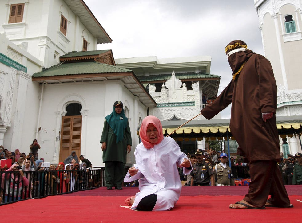 Nur Elita  screams during caning as part of her sentence in the courtyard of Baiturrahman mosque in Banda Aceh, Indonesia's Aceh province