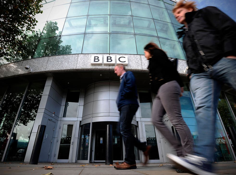 Caption:People walk past one of the entrances to the BBC Television offices in west London, on October 6, 2011