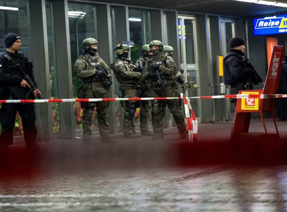 Armed police stand guard outside the evacuated railway station in Munich, Germany after reports of a 'serious' terror threat on New Year's Eve
