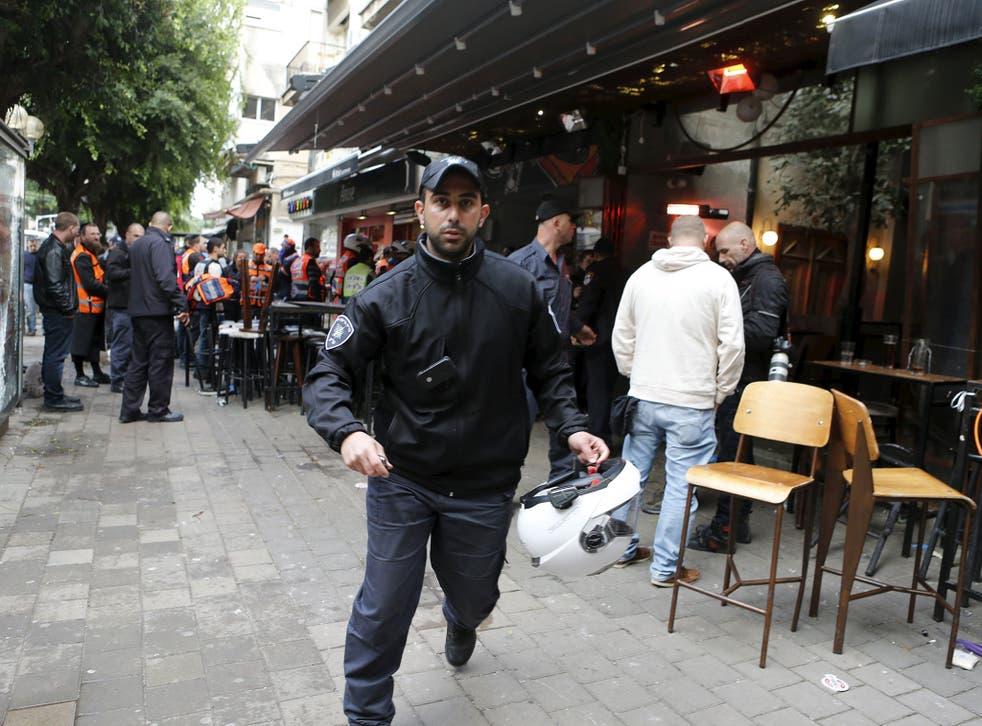 Israeli policemen run at the scene of a shooting incident in Tel Aviv, Israel, on 1 January 2016