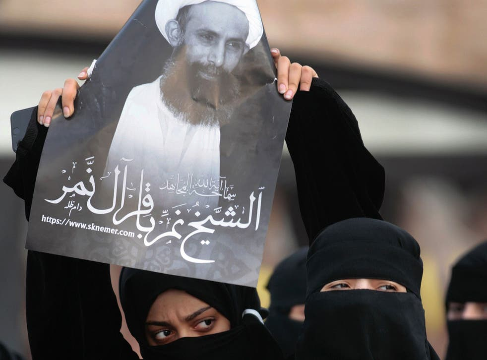 A protester holds a portrait of Sheik Nimr al-Nimr in Qatif