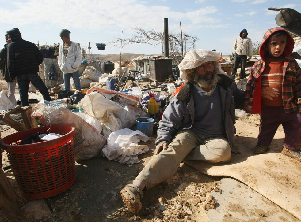 Palestinians sit with their belongings after Israeli bulldozers destroyed their home;