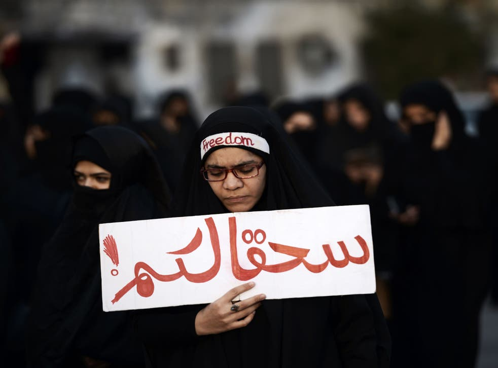 A woman in Bahrain protests against the execution of Nimr al-Nimr with the words 'Damn you'