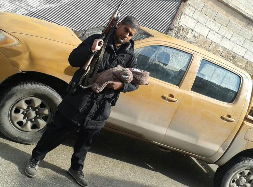 Siddhartha Dhar holds an assault rifle and his infant son soon after his arrival in Syria