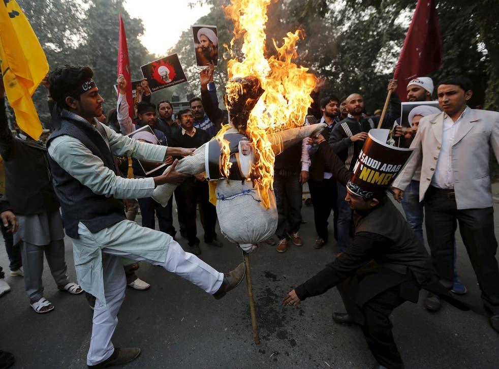 Protesters burn an effigy of Saudi King Salman bin Abdulaziz outside the Saudi embassy in India