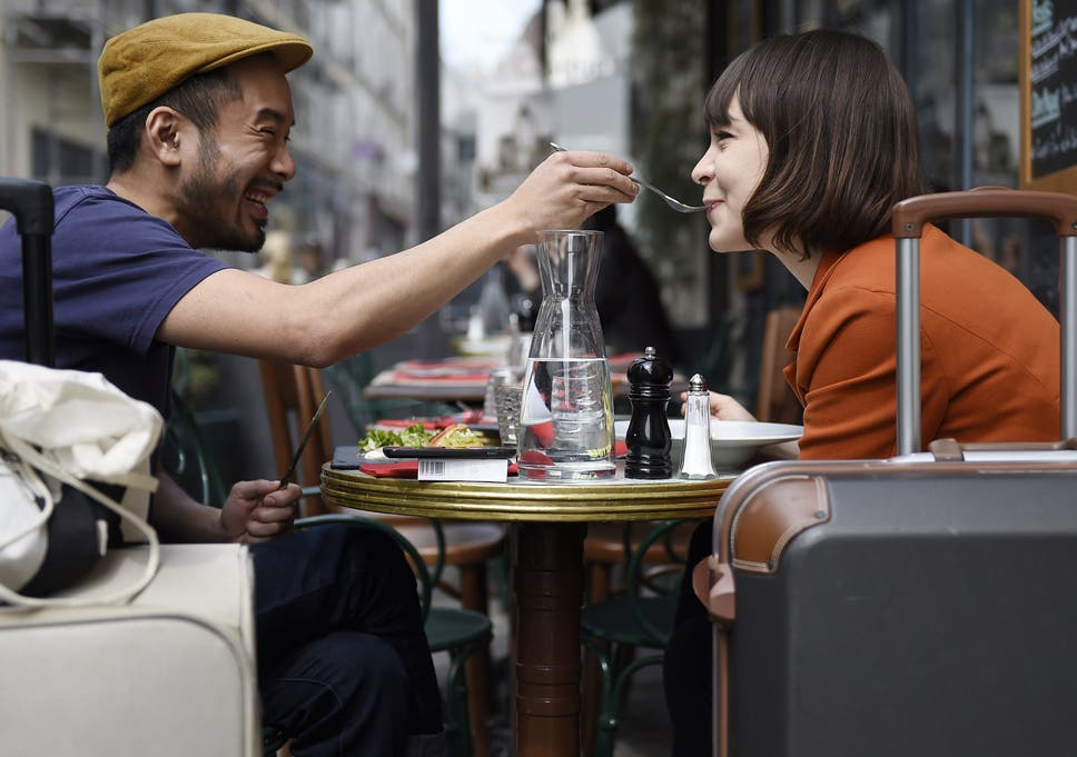 c6649002 A man feeds his partner as they eat lunch at the terrace of a restaurant in