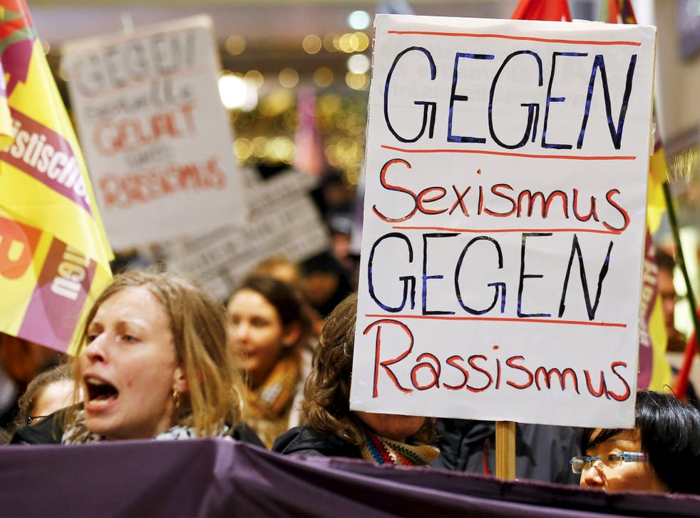 Women march through Cologne holding placards reading 'Against Sexism, Against Racism'