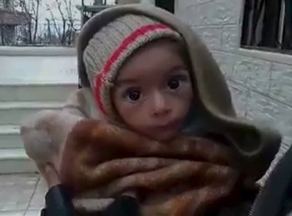 A toddler is held up to the camera in this still image taken from video said to have been shot in Madaya, Syria