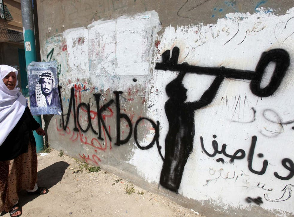 A Palestinian woman in the al-Aroub refugee camp, north of Hebron in the southern West Bank. The key in the graffiti is symbolic of the Palestinian refugee problem
