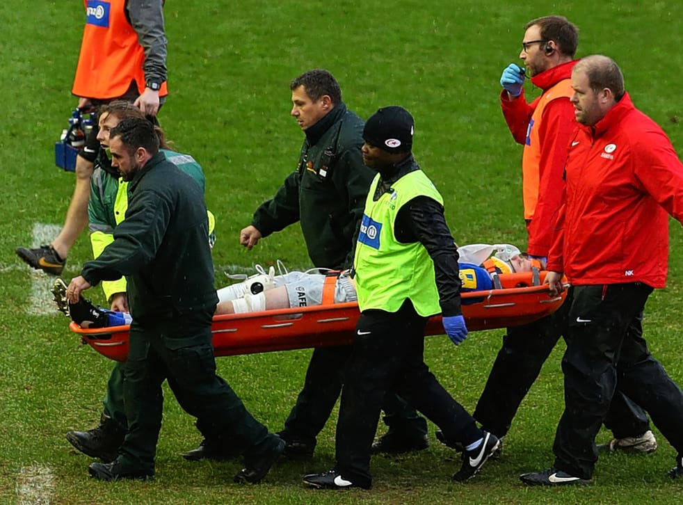 Saracens and England lock Geroge Kruis is stretchered off during yesterday's defeat to Harlequins with a suspected concussion