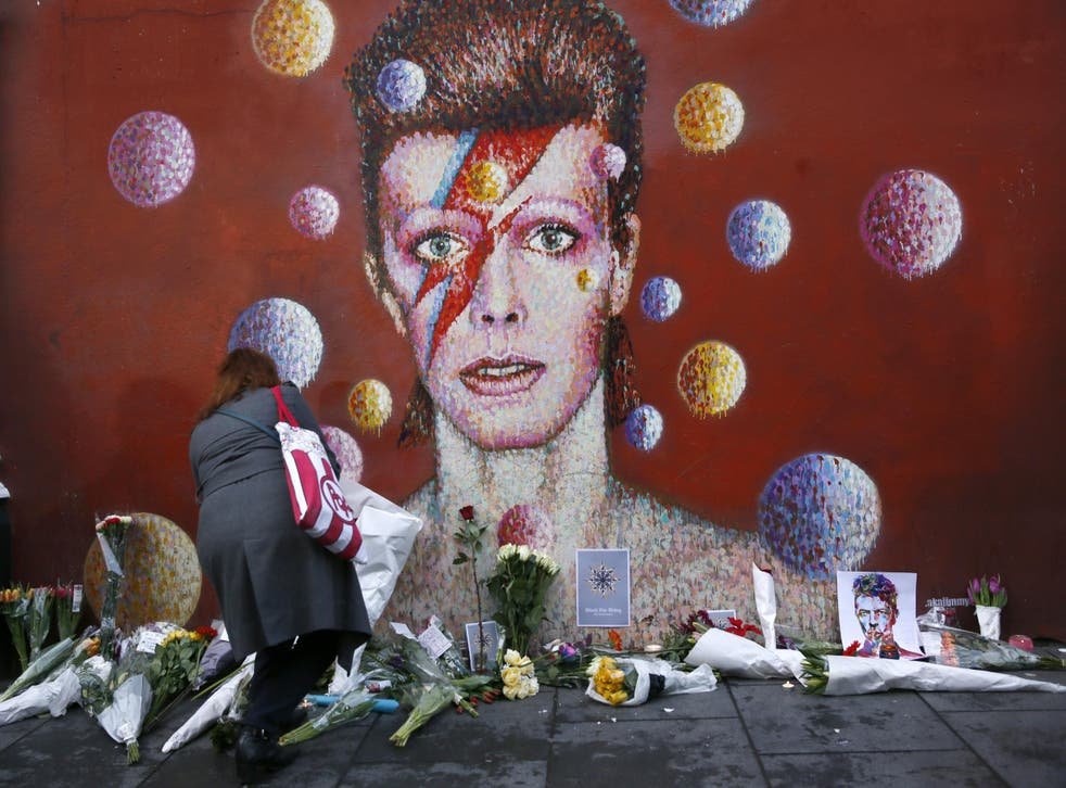 A woman leaves a bouquet at a mural of David Bowie in Brixton
