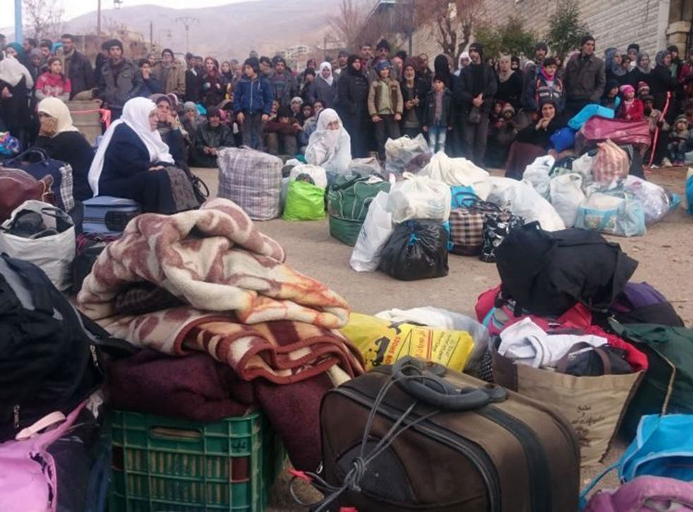 Residents of the town of Madaya wait for the UN aid convey after a six-month siege left them short of food
