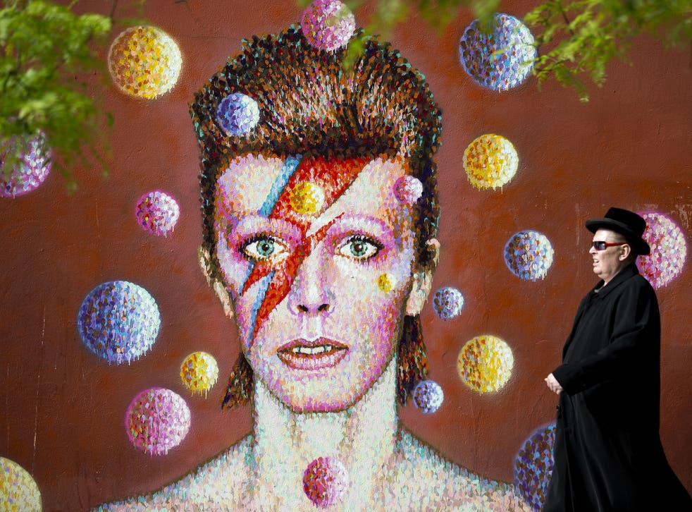 A man walks past a 3D wall portrait of British musician David Bowie, created by Australian street artist James Cochran, also known as Jimmy C, in Brixton, South London, on 19 June, 2013