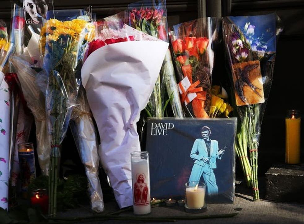Flowers, candles and pictures are some of the items deposited at a memorial outside of the late musician and performer David Bowie's apartment that he shared with his wife in New York City