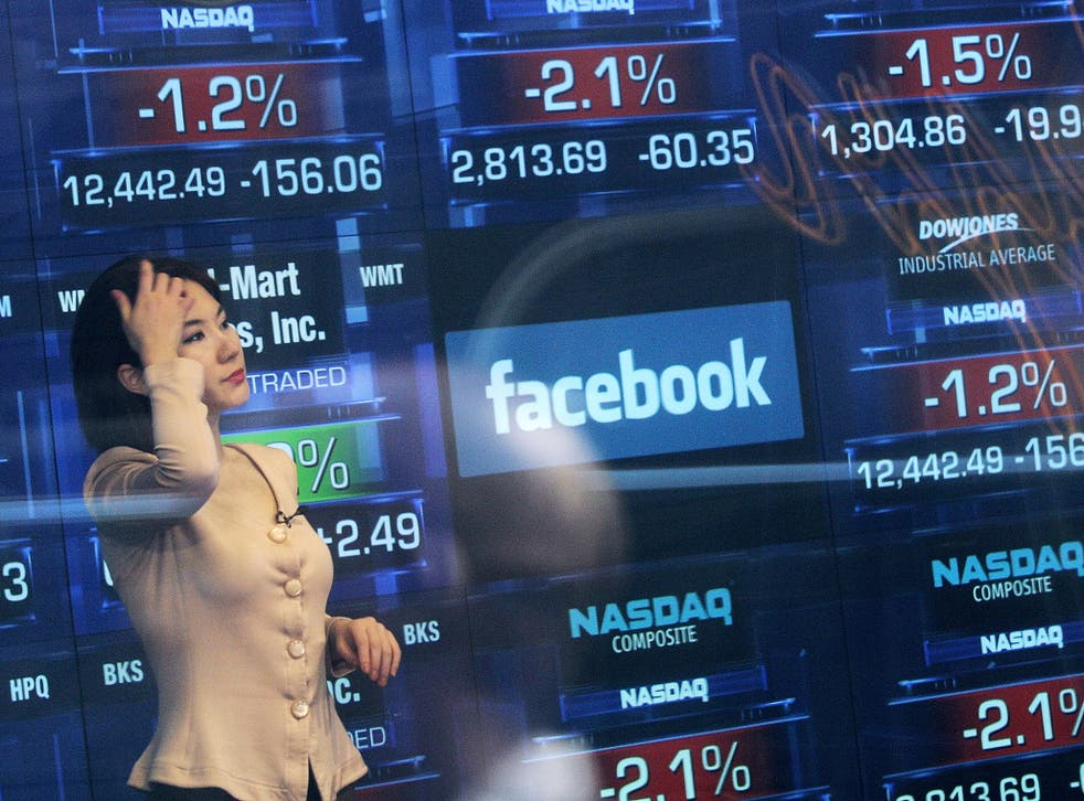 A Nasdaq television reporter is seen inside the Nasdaq studios as the Facebook logo is displayed on a ticker board on May 17, 2012 in New York City