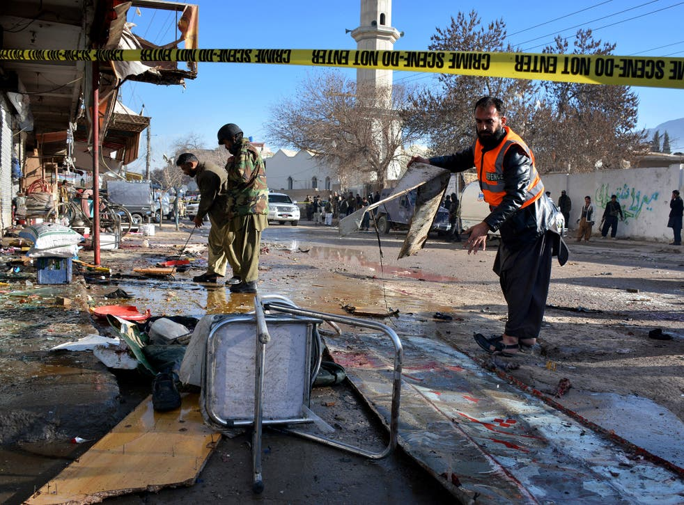 Pakistani security officials examine at the site of suicide bombing in Quetta, Pakistan. The suicide attack on a polio vaccination center in southwestern Pakistan killed more than a dozen people and wounded many, officials said.