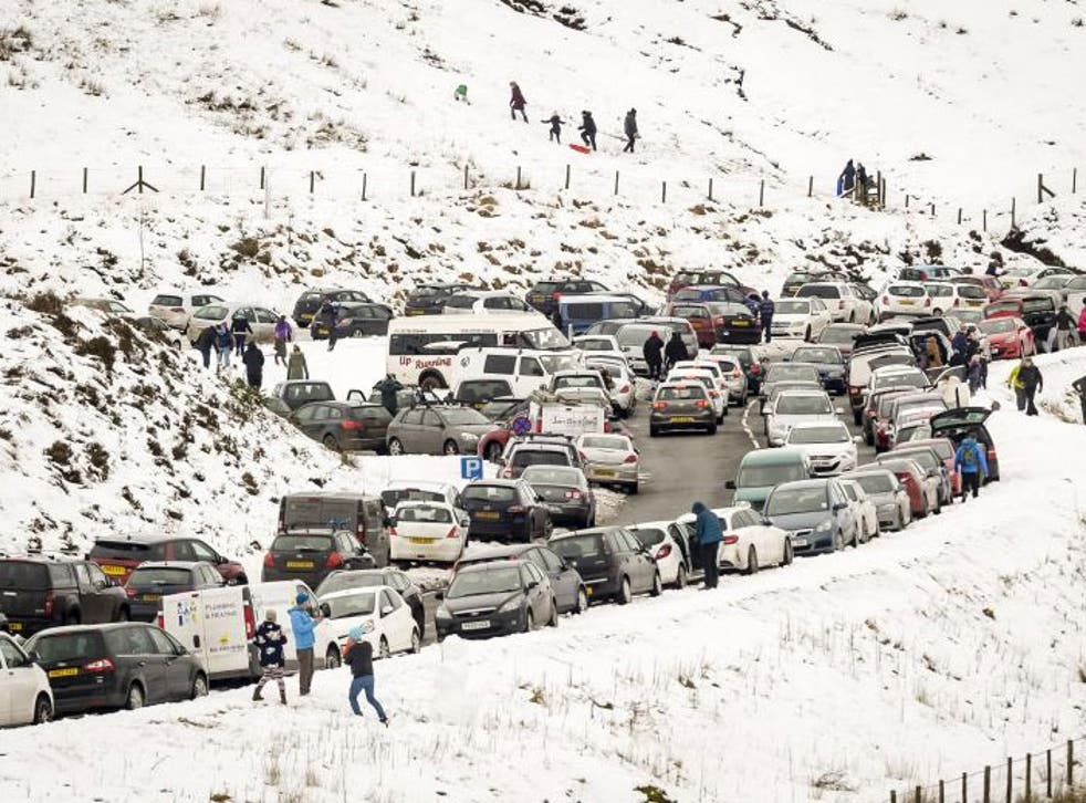 Slow moving traffic and vehicles parked on the A470, near Pen y Fan, Brecon, as people travel to the Brecon Beacons National Park to enjoy the recent snowfall