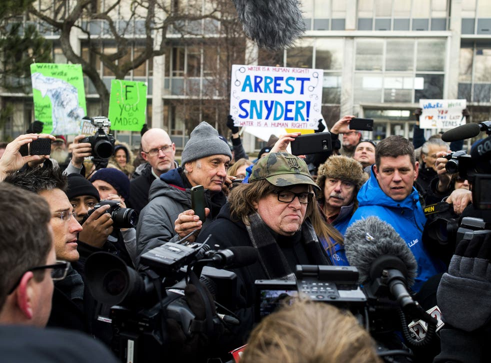 Michael Moore, centre, is part of a movement calling for the arrest of Michigan's Governor