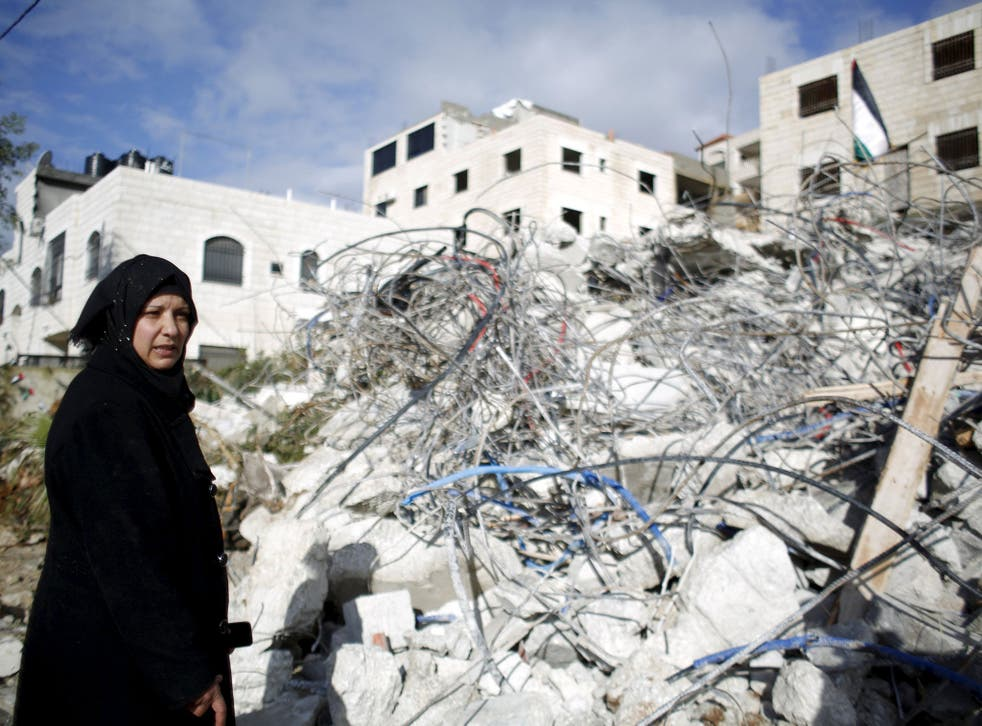 The mother of Palestinian Muhannad Halabi stands next to her house after it was demolished by Israeli troops in the village of Surda, near the West Bank city of Ramallah