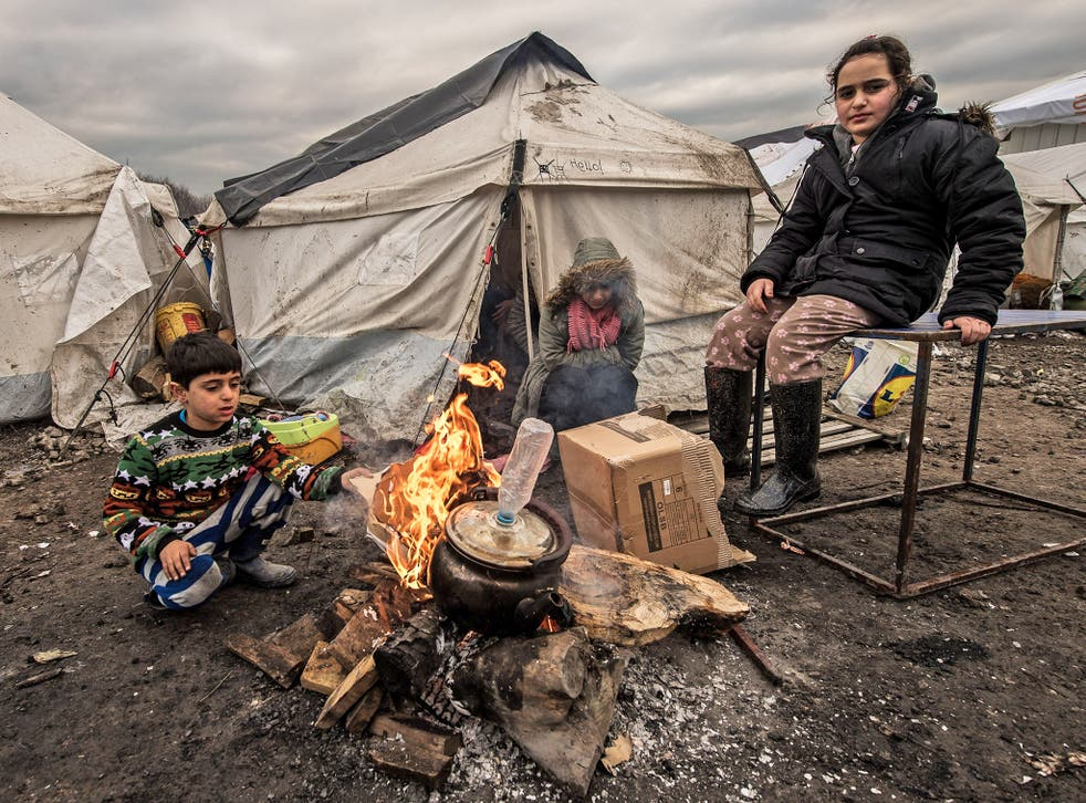 Young refugees try to keep warm at a refugee camp near Calais on Wednesday
